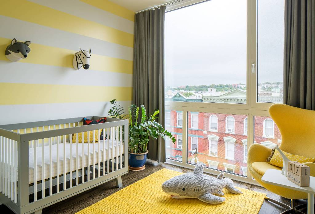 a funny nursery with a striped yellow wall, rug and a chair, grey and white furniture and faux taxidermy