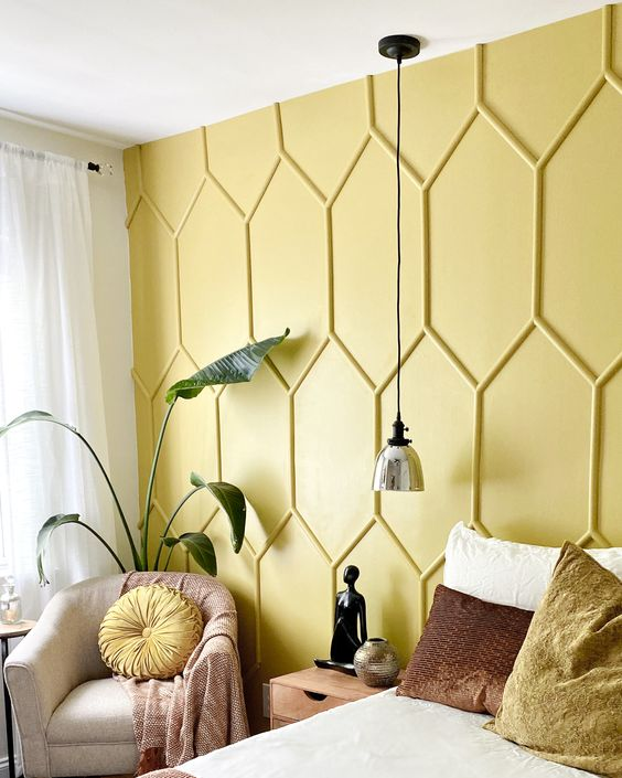a guest bedroom accented with a yellow panel wall, with comfy and chic furniture, a pendant lamp and a potted plant