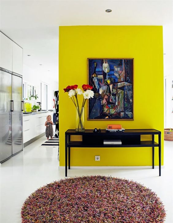 a neon yellow accent wall, a bold artwork adna vintage console table with blooms to make use of this awkward nook