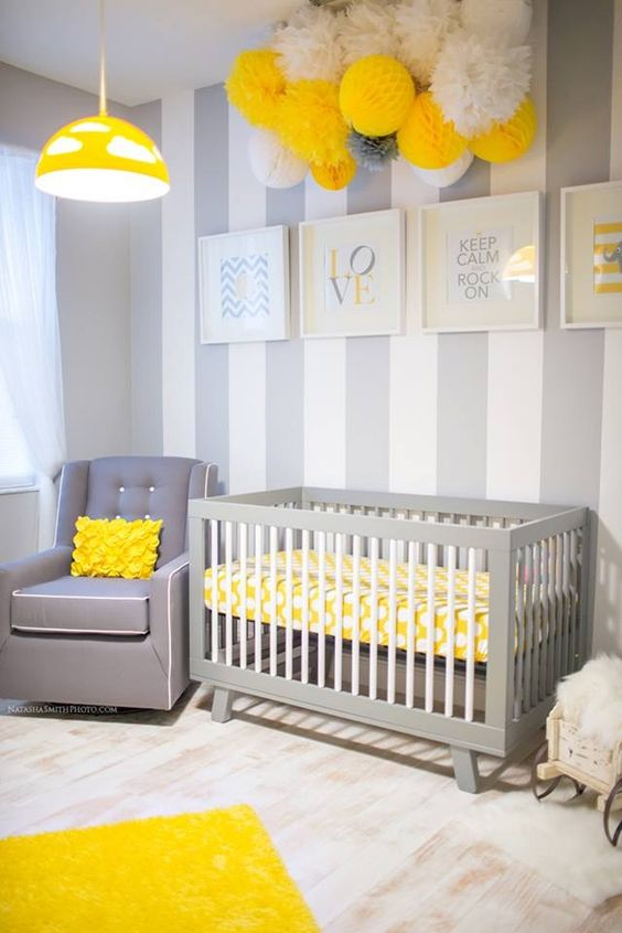 a pretty grey, white and yellow nursery with a striped accent wall, grey furniture, lots of paper pompoms and a yellow pendant lamp