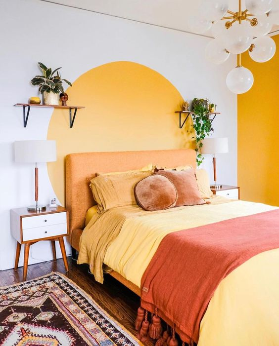 a retro bedroom with a yellow accent wall and a color block one, with an orange bed, pretty nightstands, vintage lamps and a boho rug