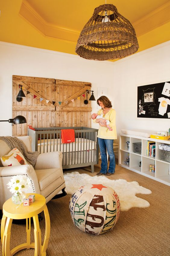 a rustic nursery with a yellow ceiling, grey and white furniture, a wooden door, a colorful ottoman and yellow touches