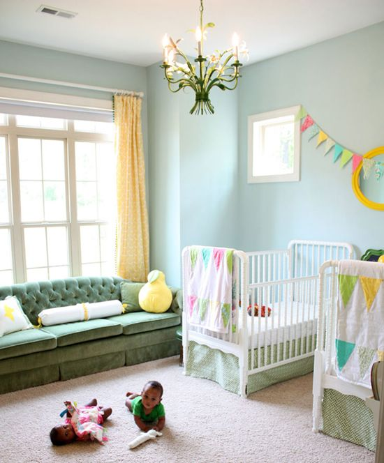 a shared nursery with light blue walls, a green sofa, white cribs, a colorful banner and bedding, bold yellow touches and a floral chandelier