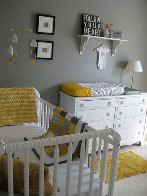 a simple and cool grey and white nursery accented with yellow linens, with modern furniture and a small gallery wall