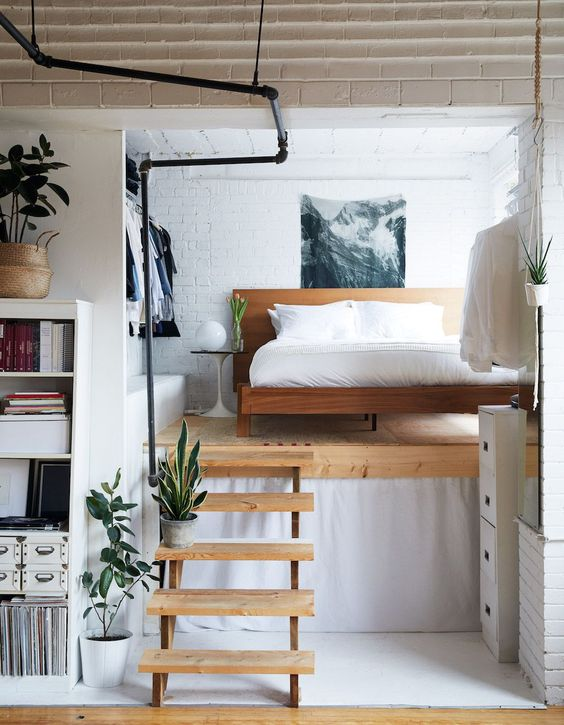 a small and chic modern loft bedroom with a wooden bed, an open closet and a cool artwork is a bold idea