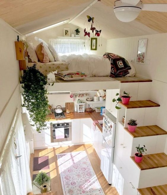 a small house with a loft bedroom and a storage stairs plus a kitchen down contains everything you may need for living