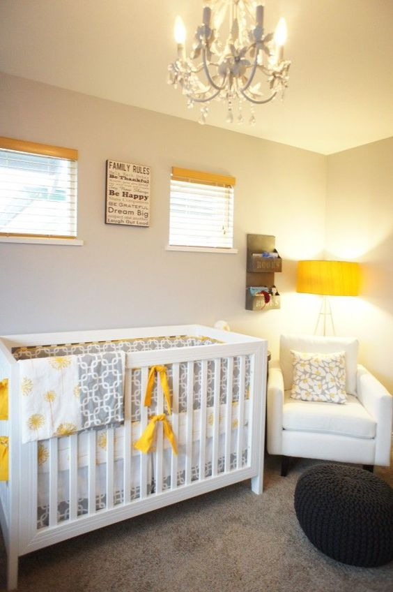 a small neutral nursery with white furniture, a black ottoman, grey printed textiles and touches of yellow here and there