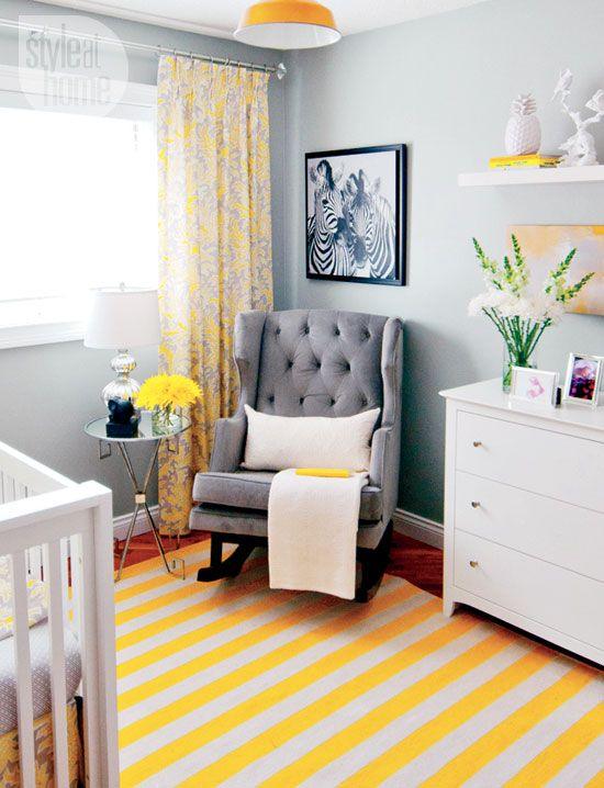 a small nursery with grey walls, white and grey furniture, a dresser, an open shelf, a printed rug and curtains, a yellow pendant lamp