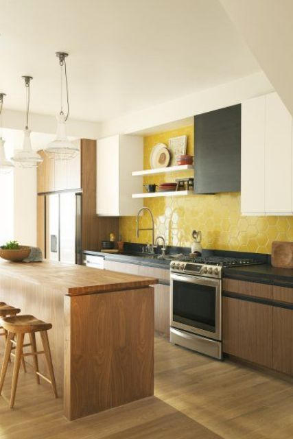 a stylish modern kitchen with black, white and stained cabinets, open shelves and a bold yellow hex tile backsplash plus a kitchen island