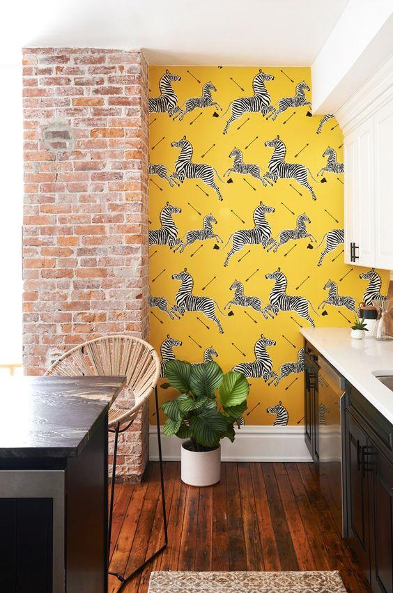 a stylish retro kitchen with black and white cabinetry, a black kitchen island, a brick pillar and yellow zebra wallpaper