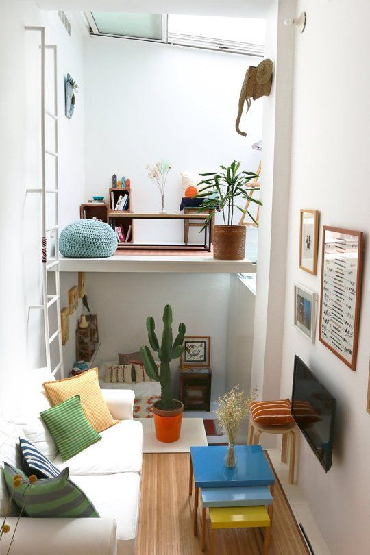 a tiny colorful apartment with a living room, a bedroom down and a loft workspace with a skylight over it is fun