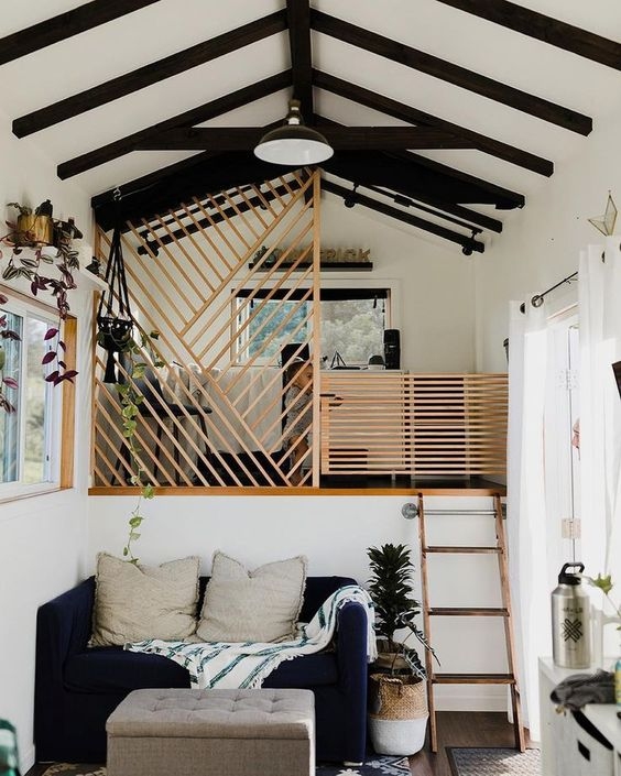 a tiny contrasting house with a living room and a bedroom up the stairs, with wooden screens to cover the space