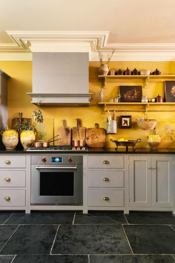 a vintage kitchen with grey cabinetry, black countertops, a yellow accent wall and open shelves with pretty artworks