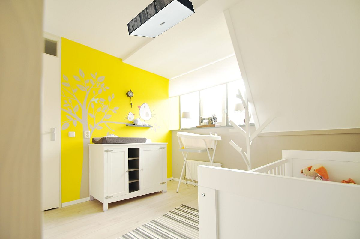 a vivacious yellow and white nursery with a painted accent wall in yellow, wihte furniture, a striped rug and a comfy lamp is wow