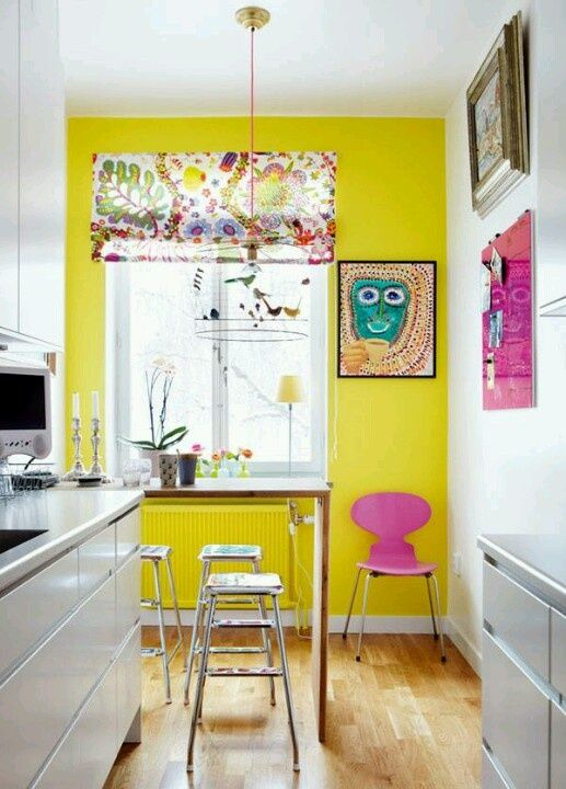 a whimsical kitchen with a shiny yellow wall, bold artworks, a console table and stools, a floral shade on the window