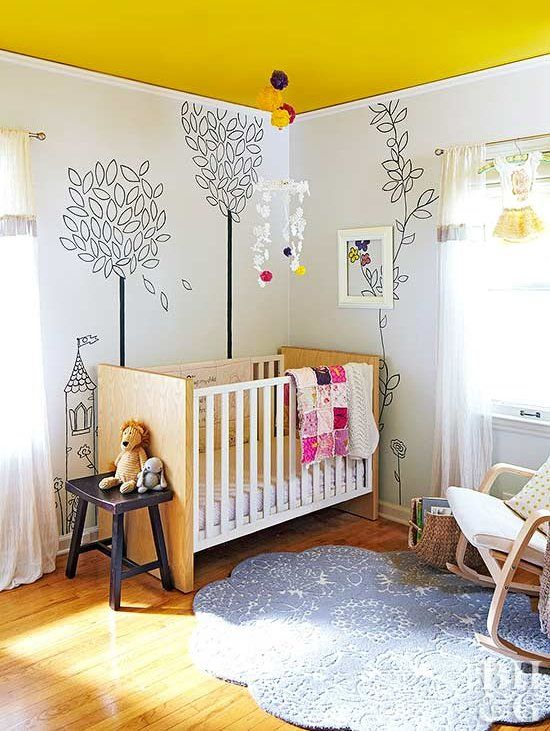 a whimsy nursery with a yellow ceiling, simple furniture, painted walls, a blue rug, bold textiles and toys