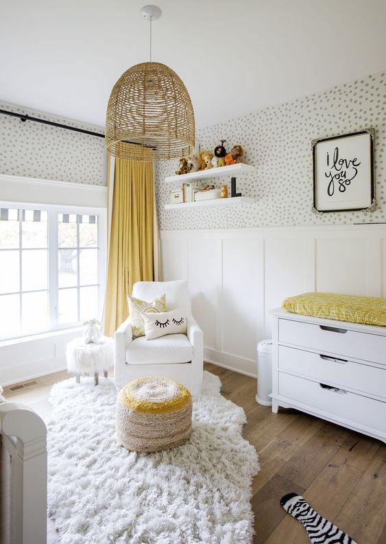 an airy and funny nursery with spot wallpaper, white furniture, a wicker lamp and some yellow touches - linens and an ottoman