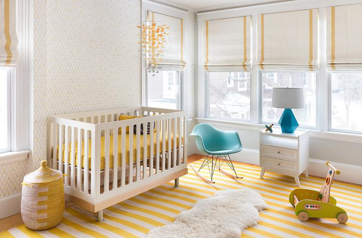 an airy nursery with white walls, a striped yellow rug, a crib with yellow bedding, some toys and Roman shades with yellow stripes