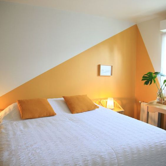 two color block accent walls in yellow and white here solve the problem of a low ceiling making it look a bit taller than it is