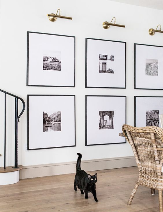 a statement grid gallery wall with matching black frames and black and white artworks with matting is a stylish idea to rock