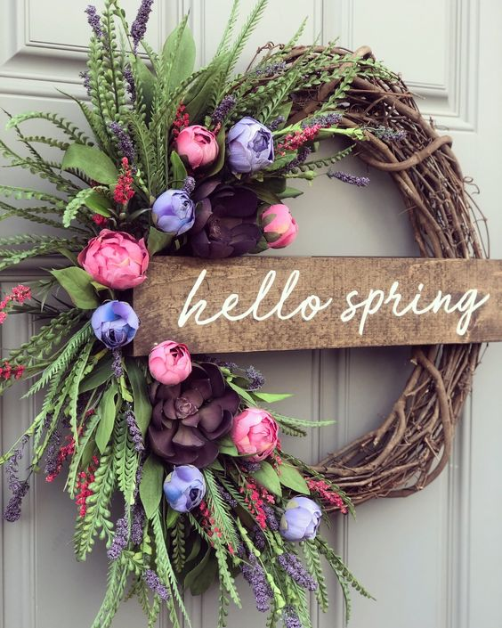 a bright and fun spring wreath of vine, a wooden plaque, bold pink, purple and blue blooms of paper and lush greenery is cool