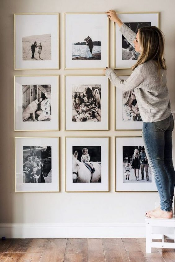 a stylish and elegant gallery wall with black and white family pics in gilded frames is a pretty solution for your home