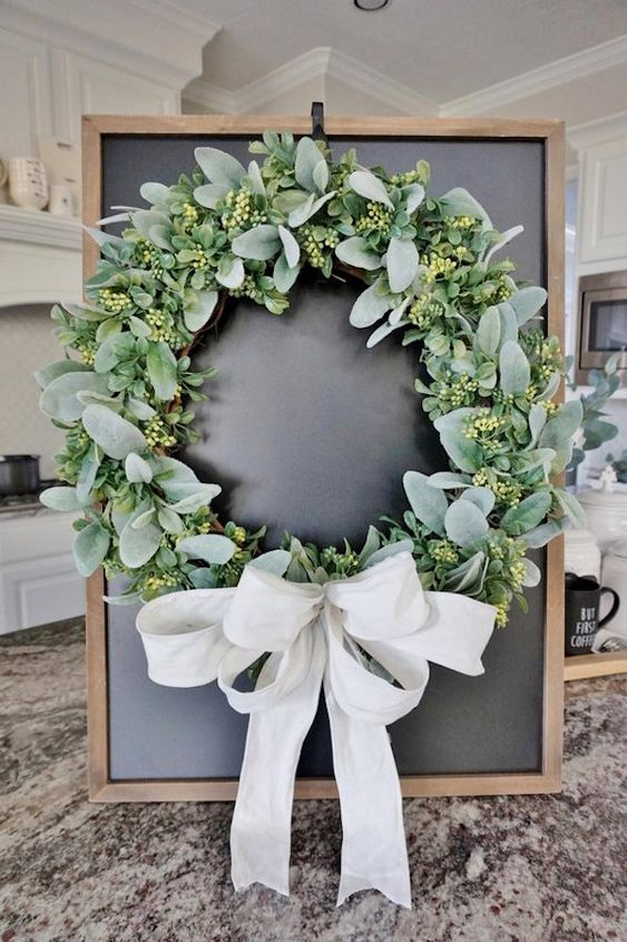 a classic greenery wreath with a large white bow is a lovely farmhouse or rustic idea for your front door