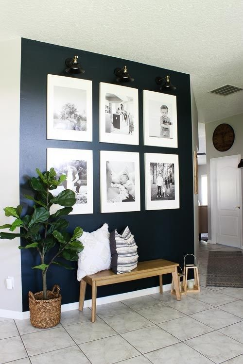 a stylish grid gallery wall with matching white frames and lights to accent it is a cool idea with a modern feel