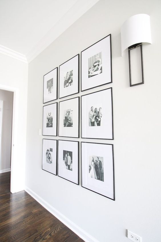 a chic and elegant grid gallery wall with black and white family pics and thin black frames is an adorable solution