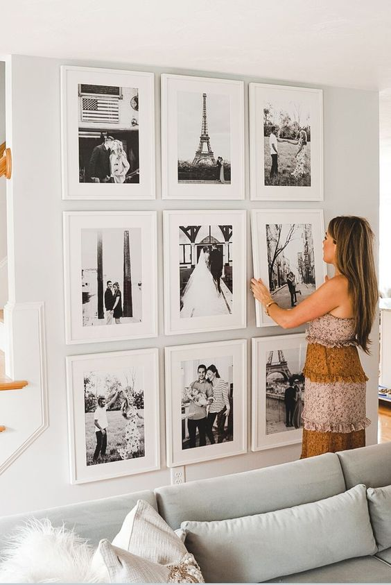 a chic grid gallery wall with matching white frames and black and white family pics is cool