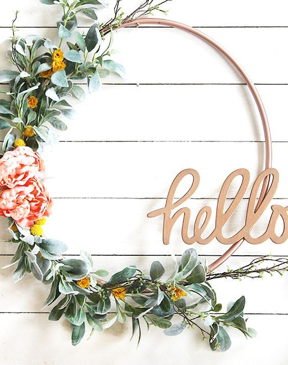 a cute spring wreath of a hoop, faux greenery, yellow and pink blooms and a HELLO calligraphy piece