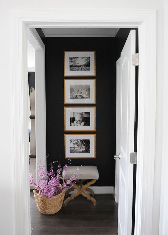 a cool one row grid gallery wall with stained wooden frames and black and white family pics - the shape gives the gallery wlal a modern look