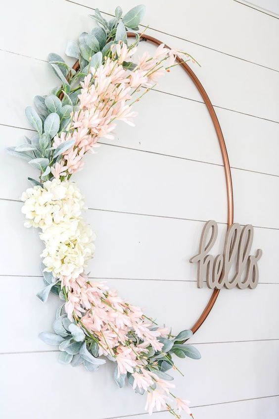a fresh and pretty spring wreath of a large hoop, faux greenery, white and pink blooms and with a HELLO piecde