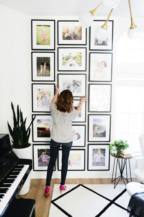 a creative grid gallery wall with matching black frames and colored family pics is a cool idea for a modern space