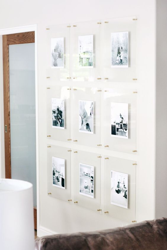 a floating gallery wall with clear acrylic frames and gold pins is a stylish idea that looks ultra-modern and outstanding