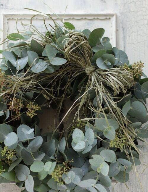 a greenery and grass wreath with seeds is a very fresh and natural idea for a modern space