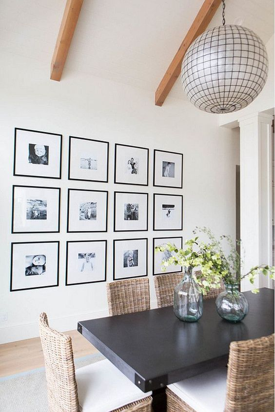 a grid gallery wall with matching black frames and clear space instead of matting and black and white photos