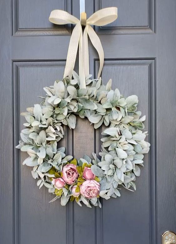 a lovely and simple spring wreath of pale greenery, pink faux blooms and a neutral ribbon bow is chic