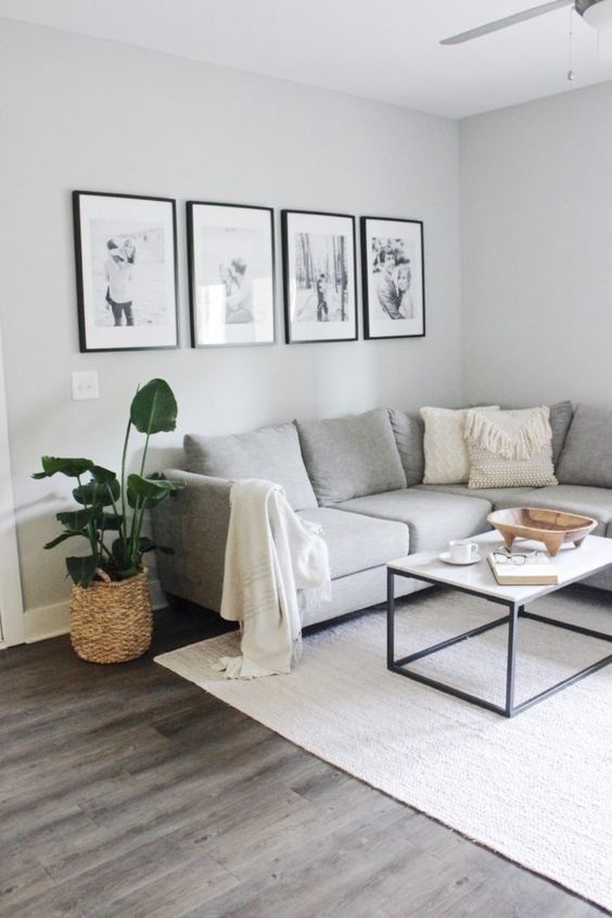a grid gallery wall with matching black frames and matting plus black and white family photos is a cool idea