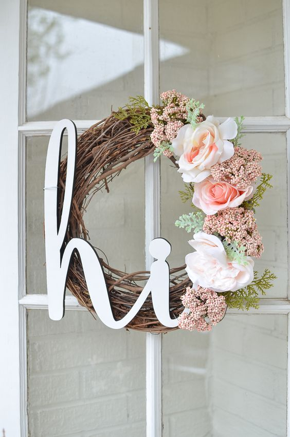 a lovely spring wreath of vine, with a calligraphy piece, pink and blush blooms and some greenery is chic