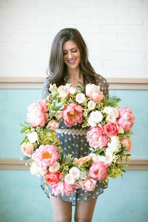 a lush artificial pink flower wreath with some white blooms and greenery is a great idea for spring and it will last long
