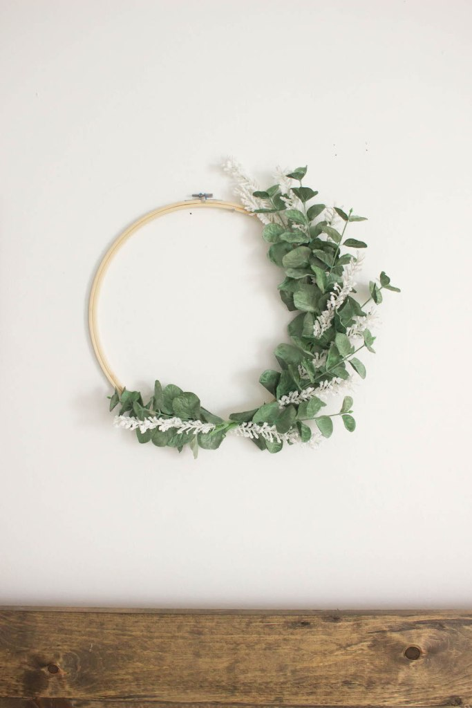 a minimalist spring wreath of a hoop, faux greenery and white branches is a pretty and very fresh decor idea