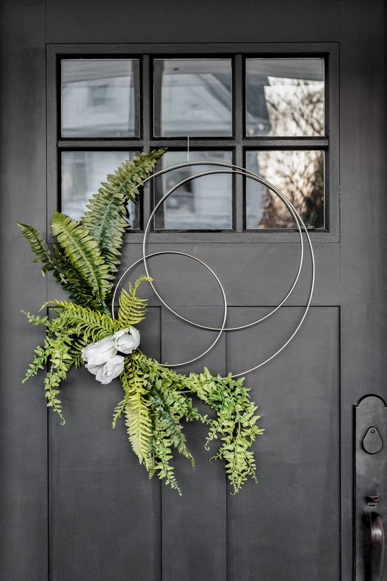 a modern and creative hoop spring wreath with ferns and some artificial blooms is very fresh and cool idea