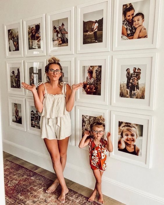 a modern gallery wall with white frames and colorful family pics looks more contemporary thanks to a grid form and matching frames