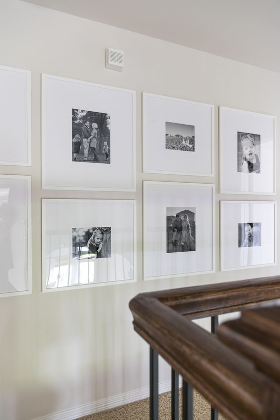 a modern grid gallery wall with white frames and black and white family pics plus white matting is fresh