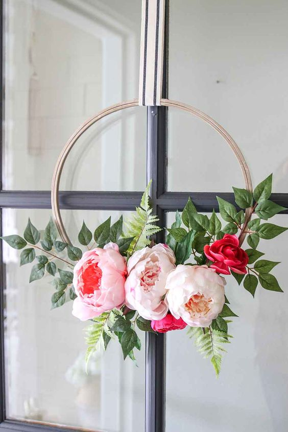 a modern spring floral wreath of a hoop, oversized blush, pink and red blooms and foliage is a gorgeous idea for spring or summer