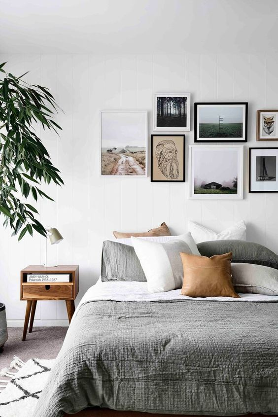 a contemporary gallery wall with a free form and mismatching frames plus prints and artworks that give it a modern feel