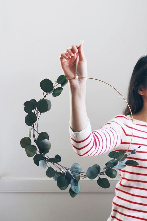 a modern spring wreath of a hoop and eucalyptus is a lovely and fresh idea in minimalist style
