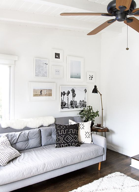 a contemporary gallery wall with a free form and mismatching white frames plus colored and black and white prints and photos