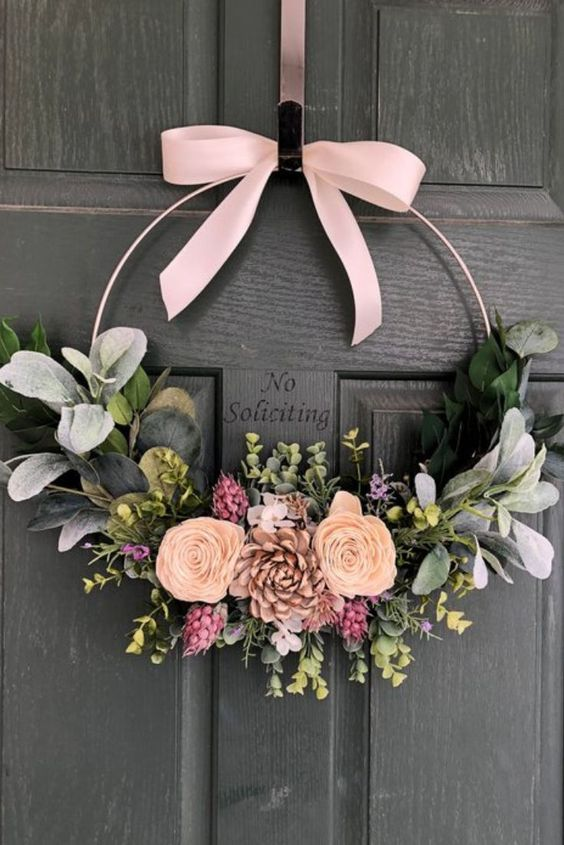a modern spring wreath of a hoop, pink ribbon bow, peachy and pink blooms, greenery is a very cute and lovely idea